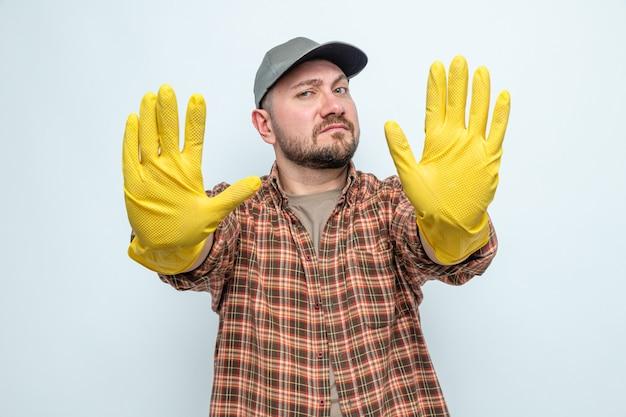 Fiducioso uomo delle pulizie slavo con guanti di gomma che allungano le mani gesticolando il segnale di stop