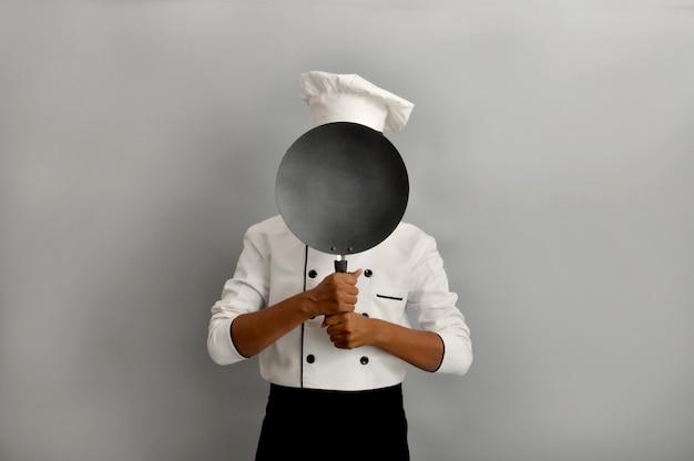 Fiducioso chef indiano sorridente che si nasconde dietro una padella su sfondo grigio professione e persone