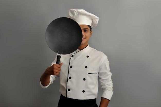 Fiducioso chef indiano sorridente che nasconde mezza faccia dietro una padella su sfondo grigio
