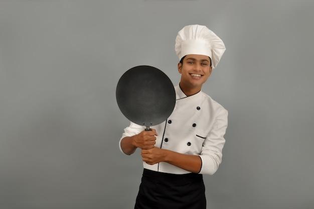 Fiducioso chef indiano sorridente che sorride dietro la padella su sfondo grigio