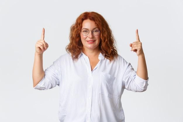 Donna di mezza età sorridente sicura con i capelli rossi, con gli occhiali e la camicetta, che punta il dito verso l'alto, che mostra pubblicità, promuove i suoi corsi online, inizia a lavorare online, muro bianco.