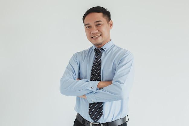 Fiducioso sorridente uomo di vendita che indossa camicia blu e cravatta in posa con le braccia piegate su sfondo bianco