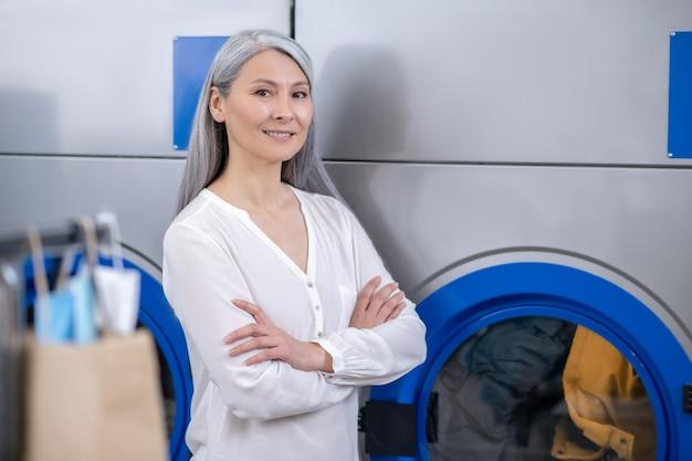 Fiduciosa donna sorridente in piedi con le braccia conserte sul petto vicino alla grande lavatrice nel lavaggio a secco