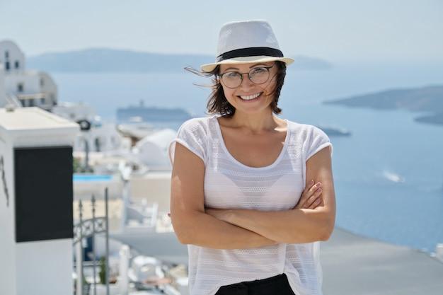 Turista sorridente sicuro della donna che viaggia sulla crociera di lusso nel mediterraneo, grecia, santorini. femmina con le braccia conserte che guarda l'obbiettivo, sfondo architettura isola mare sky