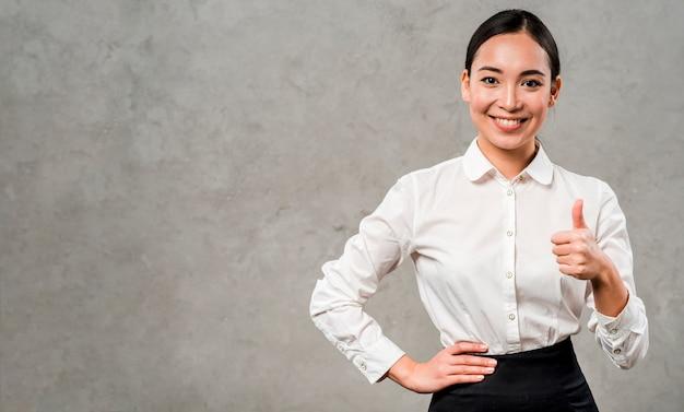 Giovane donna di affari sorridente sicura che mostra pollice sul segno che sta contro la parete grigia