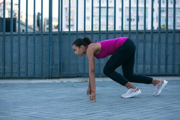 Sportiva sicura che si allena all'aperto e mette le mani a terra prima di correre