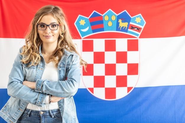 Ragazza bionda adolescente in piedi sicura di fronte alla bandiera croata.