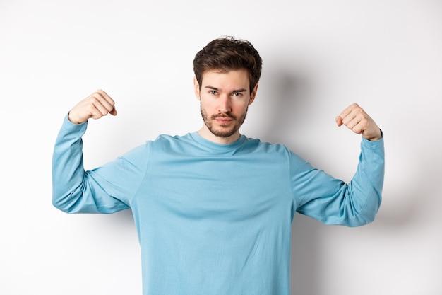 Uomo macho sicuro e forte che flette i bicipiti, mostrando la forza nei muscoli dopo l'allenamento in palestra, in piedi su sfondo bianco.