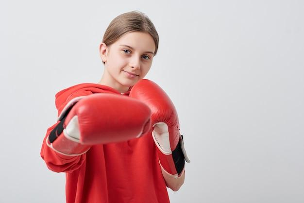 Fiducioso e forte ragazza adolescente in rosso activewear e guantoni da boxe facendo calcio mentre si esercita davanti alla telecamera in isolamento