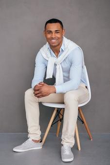 Fiducioso e di successo. fiducioso giovane africano seduto sulla sedia