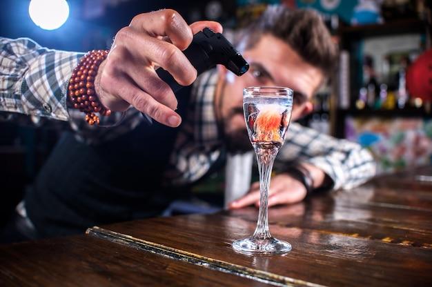 Il tapster fiducioso decora l'intruglio colorato mentre è in piedi vicino al bancone del bar in un pub