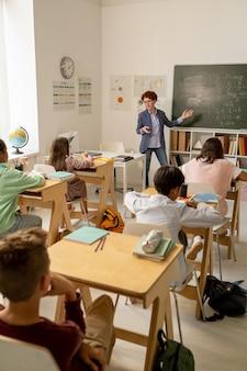 Insegnante fiducioso che spiega la nuova formula degli scolari tramite la lavagna