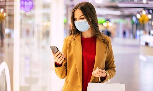 Fiduciosa donna alla moda in una mascherina medica di sicurezza con una borsa della spesa e smart phone sta camminando nel centro commerciale