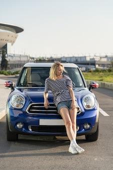 Fiducioso proprietario di un'auto donna in un'auto moderna al di fuori degli edifici urbani del centro di concessionarie automobilistiche