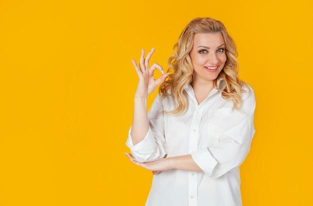 Fiduciosa donna vestita con una camicia bianca, sorridendo ampiamente, mostrando bene, bene, gesto, buon umore