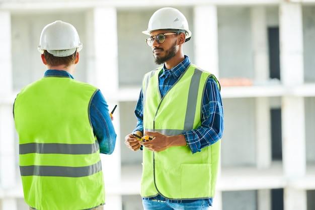 Lavoratore sicuro che ascolta i colleghi al sito della palazzina di appartamenti