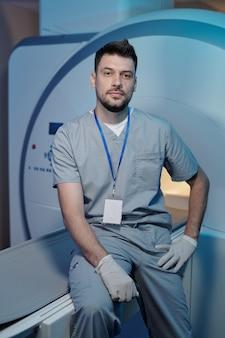 Fiducioso lavoratore del laboratorio medico seduto sul tavolo dell'attrezzatura ct