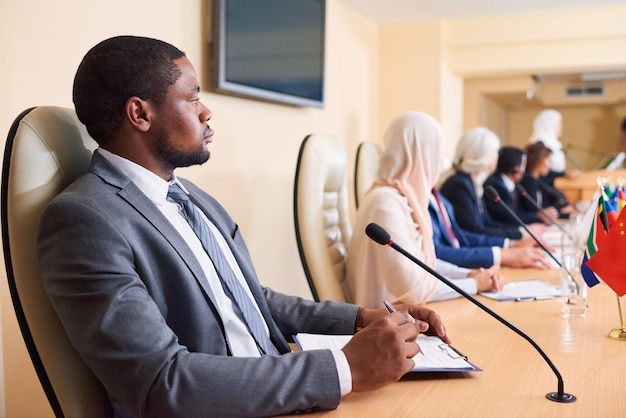 Fiducioso giovane delegato afro-americano in abiti da cerimonia seduti a tavola con colleghi stranieri alla conferenza