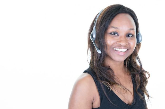 Scrittorio d'uso della cuffia avricolare dell'agente di servizio di assistenza al cliente della giovane donna africana sicura Foto Premium