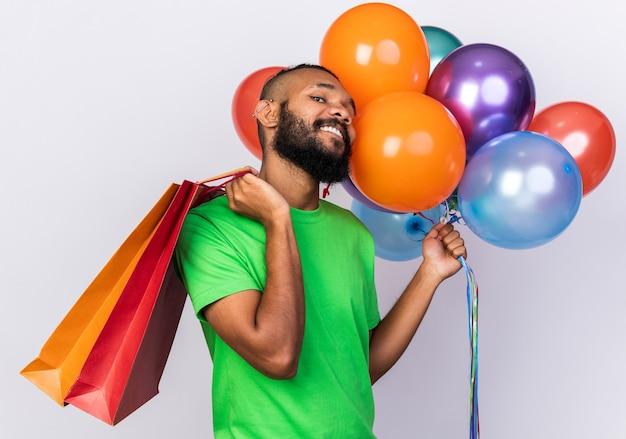 Fiducioso giovane ragazzo afro-americano che indossa un cappello da festa con palloncini che mettono la borsa regalo sulla spalla