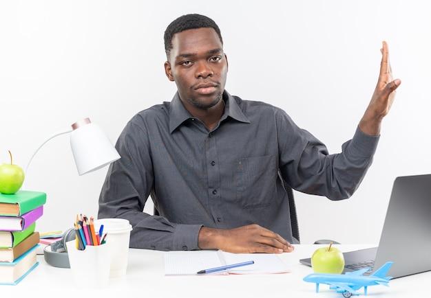 Fiducioso giovane studente afroamericano seduto alla scrivania con gli strumenti della scuola che tiene la mano aperta gesticolando il segnale di stop isolato sul muro bianco