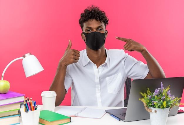 Fiducioso giovane studente afroamericano che indossa e indica la sua maschera facciale seduto alla scrivania con gli strumenti della scuola che sfogliano isolato sul muro rosa
