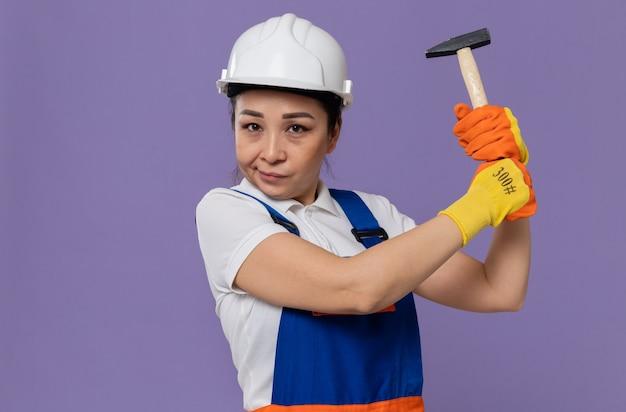 Fiduciosa giovane ragazza asiatica del costruttore con casco di sicurezza bianco e guanti che tengono martello