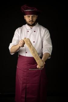 Fiducioso giovane fornaio maschio barbuto che indossa grembiule viola e cappuccio che tiene pane baguette fresco