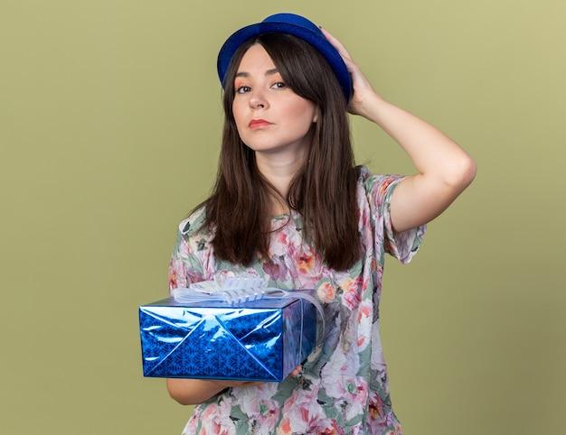 Fiduciosa giovane bella ragazza che indossa un cappello da festa che tiene in mano una scatola regalo mettendo la mano sulla testa isolata sul muro verde oliva