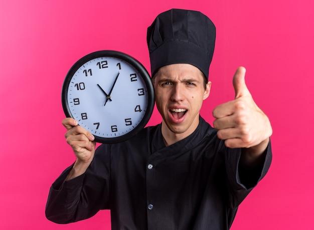 Fiducioso giovane cuoco maschio biondo in uniforme da chef e berretto che tiene l'orologio che tocca il viso con esso guardando la telecamera che mostra il pollice in su isolato sulla parete rosa