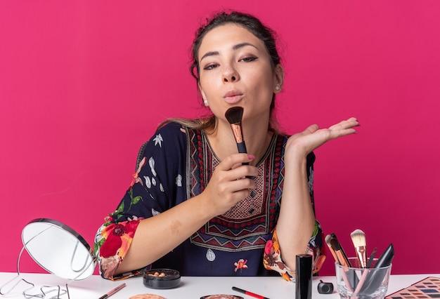 Fiduciosa giovane ragazza bruna seduta al tavolo con strumenti per il trucco che tiene il pennello per il trucco isolato sulla parete rosa con spazio per le copie