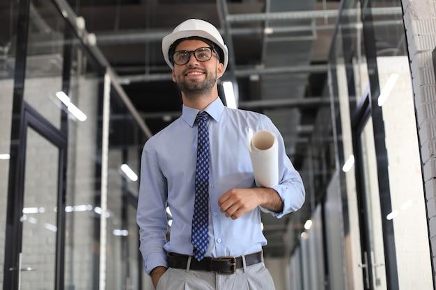 Fiducioso giovane uomo d'affari in elmetto protettivo che tiene il progetto e distoglie lo sguardo mentre si sta in piedi al chiuso.