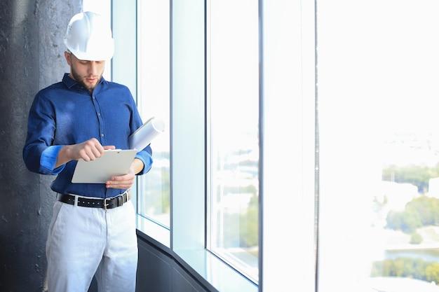 Fiducioso giovane uomo d'affari in elmetto protettivo che tiene il progetto e guarda i documenti mentre si sta in piedi al chiuso.