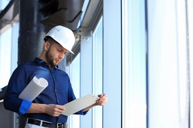 Fiducioso giovane uomo d'affari in elmetto protettivo che tiene il progetto e guarda i documenti mentre si trova in casa.