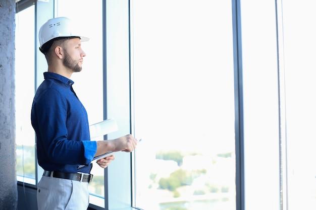 Fiducioso giovane uomo d'affari in camicia esaminando il progetto mentre in piedi contro una finestra in ufficio.