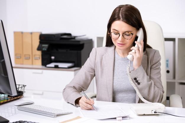 Fiduciosa giovane imprenditrice seduto al tavolo e prendere appunti nel documento mentre discute il contenuto del contratto per telefono
