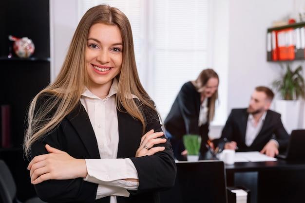Fiduciosa giovane imprenditrice in piedi con le braccia incrociate in un ufficio moderno con i colleghi che lavorano in background Foto Premium