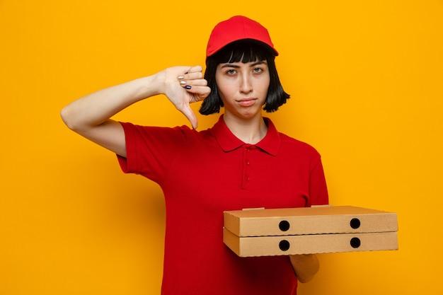 Fiduciosa giovane ragazza delle consegne caucasica che tiene in mano scatole per pizza e fa il pollice verso il basso