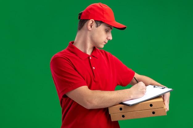 Fiducioso giovane fattorino caucasico in camicia rossa che tiene appunti su scatole per pizza e scrive con penna