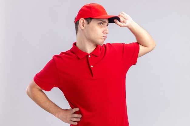 Fiducioso giovane fattorino caucasico in camicia rossa che tiene il berretto e guarda il lato isolato sul muro bianco con spazio di copia
