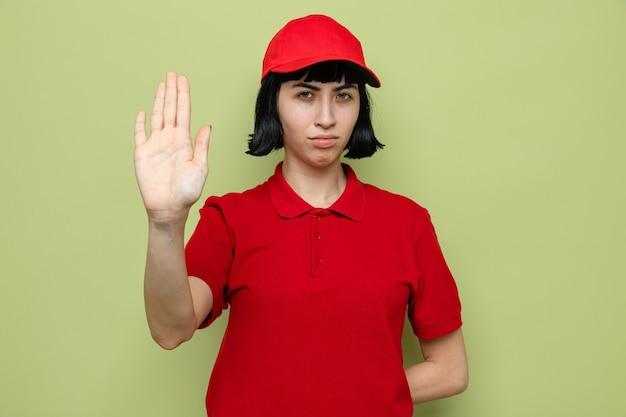 Fiduciosa giovane donna di consegna caucasica che gesturing il segnale di stop