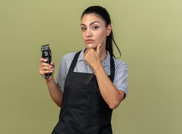 Fiducioso giovane barbiere femmina caucasica che indossa l'uniforme che tiene i tagliacapelli tenendo la mano sotto il mento isolata sulla parete verde oliva con spazio di copia
