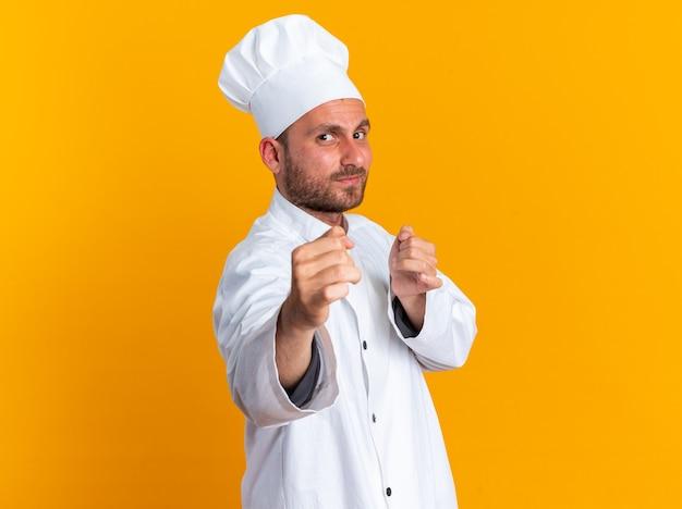 Fiducioso giovane maschio caucasico cuoco in uniforme da chef e berretto in piedi in vista di profilo guardando la telecamera facendo gesto di boxe isolato sulla parete arancione con spazio di copia