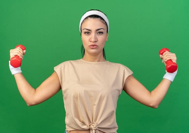 Fiducioso giovane caucasica ragazza sportiva che indossa fascia e braccialetti sollevando i manubri guardando la parte anteriore isolata sulla parete verde