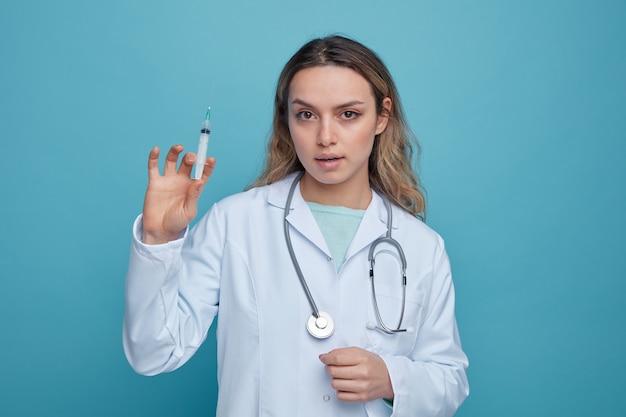 Fiducioso giovane medico femminile che indossa abito medico e stetoscopio intorno al collo tenendo la siringa