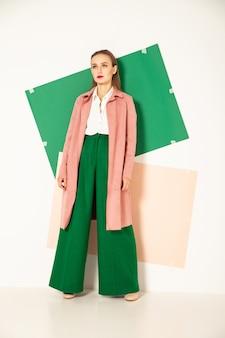 Fiducioso giovane modello femminile in elegante cappotto rosa pastello e pantaloni verde brillante che rappresentano la moda primaverile che guarda lontano in studio