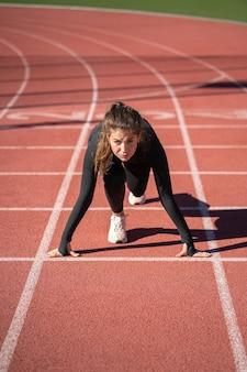 Fiducioso giovane velocista donna in forma su uno stadio di gomma tapis roulant o pista da corsa che si prepara per iniziare a correre