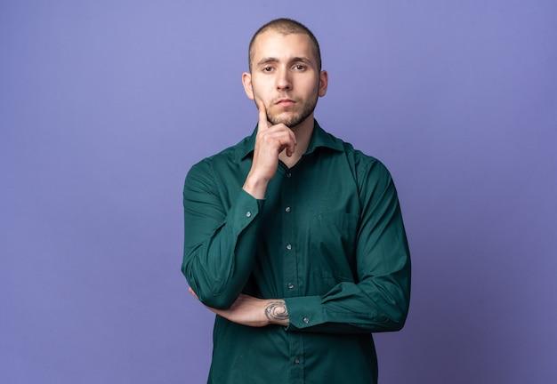 Fiducioso giovane bel ragazzo che indossa una camicia verde mettendo il dito sulla guancia