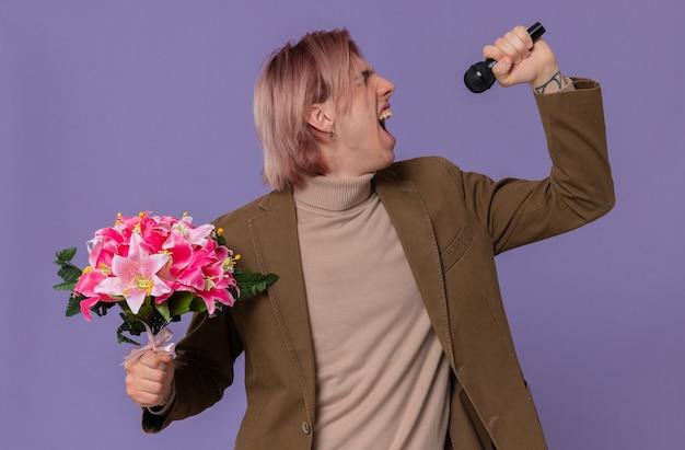 Fiducioso giovane bell'uomo con in mano un mazzo di fiori e un microfono che canta