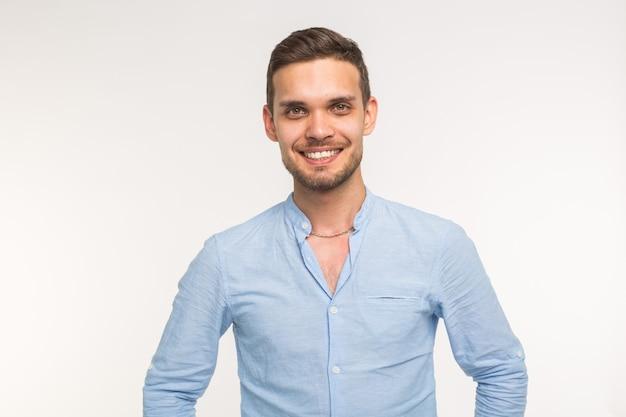 Fiducioso giovane uomo bello sorridente sul muro bianco.